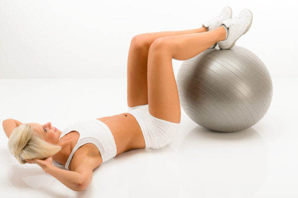 Young woman doing sit-ups on fitness ball lying white floor